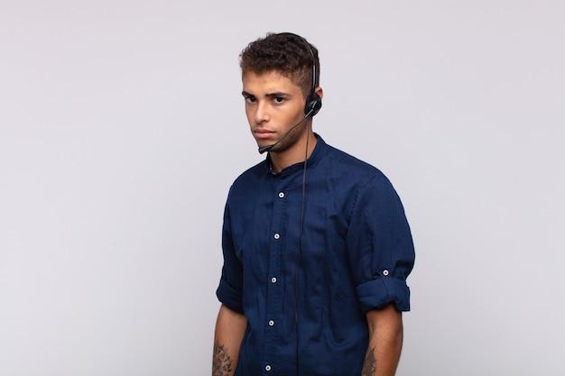 Jonge telemarketeer man die zich verdrietig, boos of boos voelt en naar de zijkant kijkt met een negatieve houding, fronst bij onenigheid