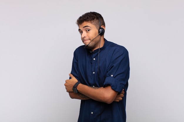 Jonge telemarketeer man die zijn schouders ophaalt, zich verward en onzeker voelt, twijfelt met gekruiste armen en een verbaasde blik