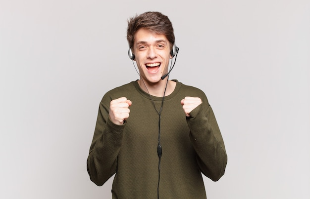 Jonge telemarketeer voelt zich geschokt, opgewonden en gelukkig, lacht en viert succes en zegt wow!