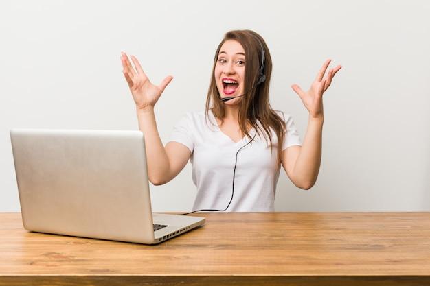 Jonge telemarketeer vrouw ontvangt een aangename verrassing, opgewonden en verhogen handen.