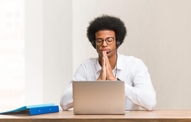 Jonge telemarketeer zwarte man bidden erg blij en zelfverzekerd