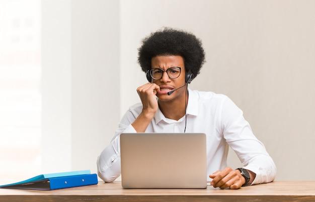 Jonge telemarketeer zwarte man nagels bijten, nerveus en erg angstig