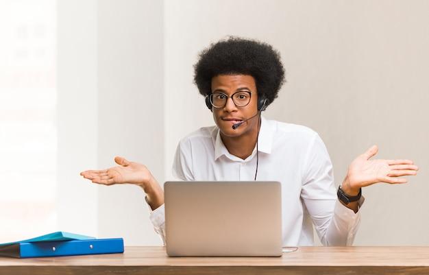 Jonge telemarketeer zwarte man verward en twijfelachtig
