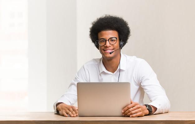 Jonge telemarketeer zwarte man vrolijk met een grote glimlach