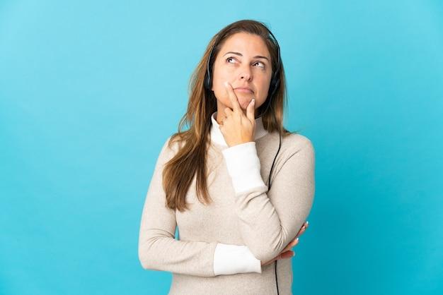 Jonge telemarketeervrouw op geïsoleerd blauw die twijfels hebben tijdens het opzoeken