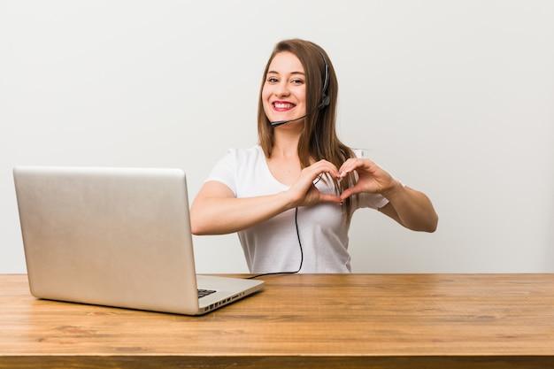 Jonge telemarketer vrouw die en een hartvorm met handen glimlacht toont
