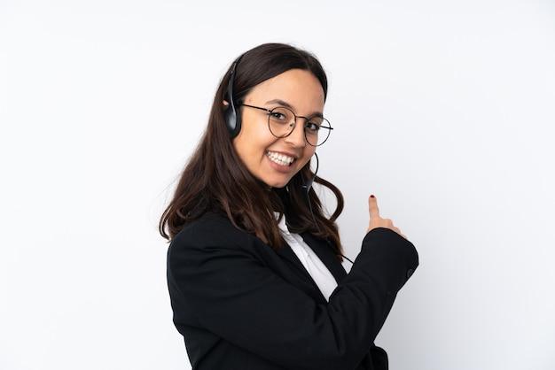 Jonge telemarketer vrouw op witte muur terug te wijzen