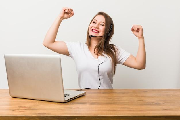 Jonge telemarketer vrouw toont kracht gebaar met armen, symbool van vrouwelijke macht