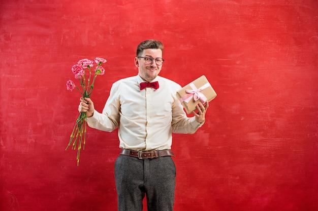 Jonge teleurgestelde grappige mens met bloemen en gift op rode studioachtergrond