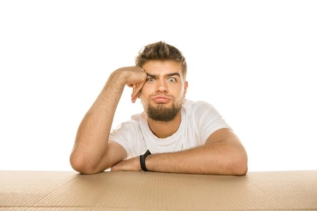 Jonge teleurgestelde man die het grootste postpakket opent dat op wit wordt geïsoleerd. geschokt mannelijk model bovenop een kartonnen doos die naar binnen kijkt.