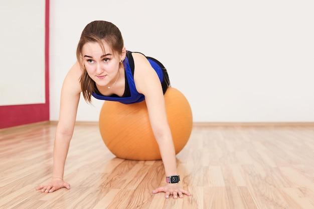Jonge tengere vrouw traint door push-up te doen met een oefenbal in de sportschool