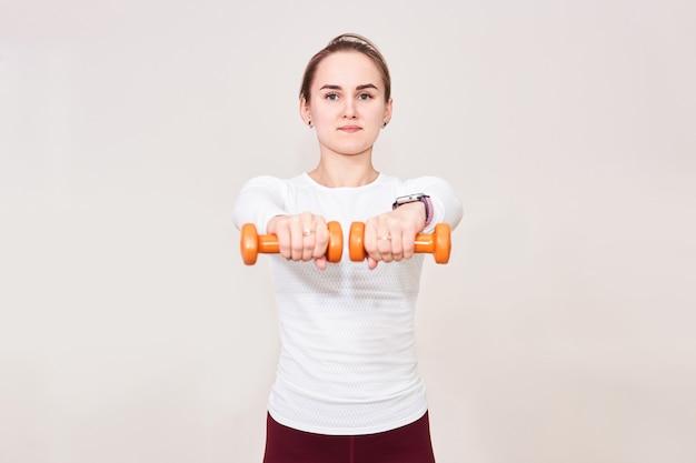 Jonge tengere vrouw voert oefeningen uit met halters die ze voor zich houden