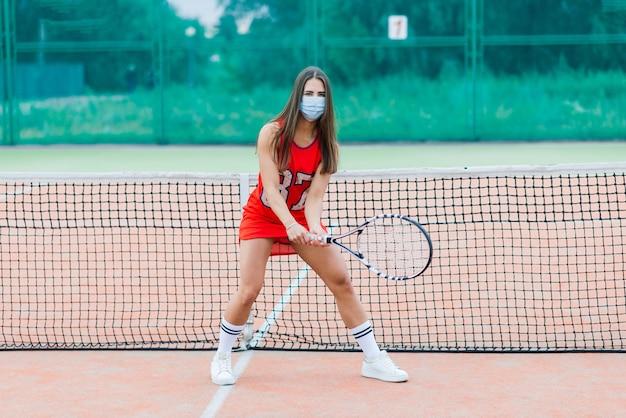 Jonge tennisser die met beschermend masker een racket houdt