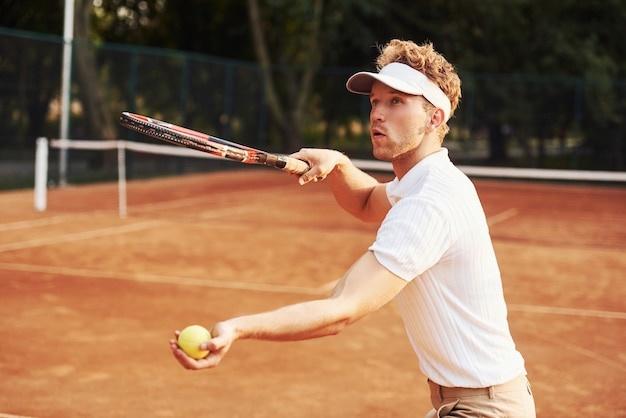 Jonge tennisser in sportieve kleding is buiten op het veld.