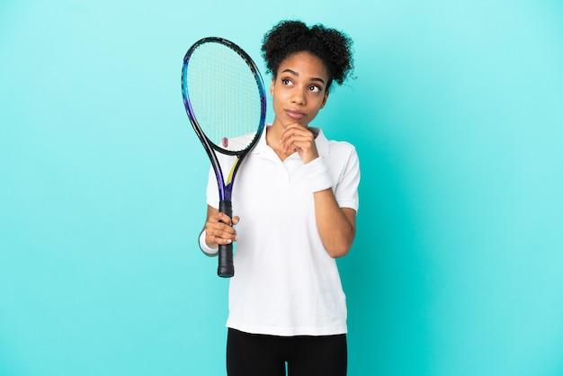 Jonge tennisser vrouw geïsoleerd op blauwe achtergrond en opzoeken