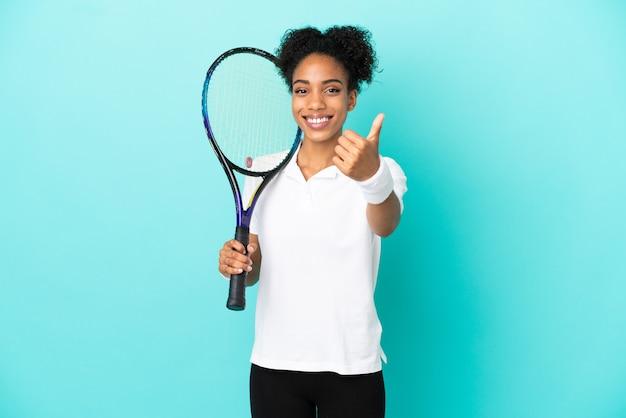 Jonge tennisser vrouw geïsoleerd op blauwe achtergrond met duimen omhoog omdat er iets goeds is gebeurd