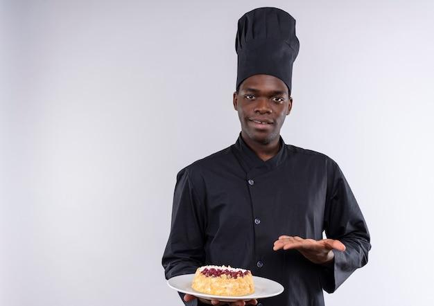 Jonge tevreden afro-amerikaanse kok in uniform chef houdt cake op plaat en punten met hand op wit met kopie ruimte
