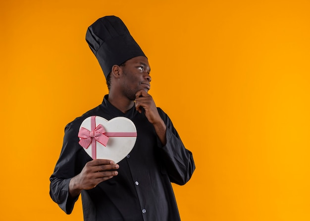 Jonge tevreden afro-amerikaanse kok in uniform chef houdt hart vorm doos en legt hand op kin op oranje met kopie ruimte