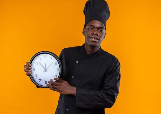 Jonge tevreden afro-amerikaanse kok in uniform chef houdt klok en kijkt naar camera op oranje met kopie ruimte