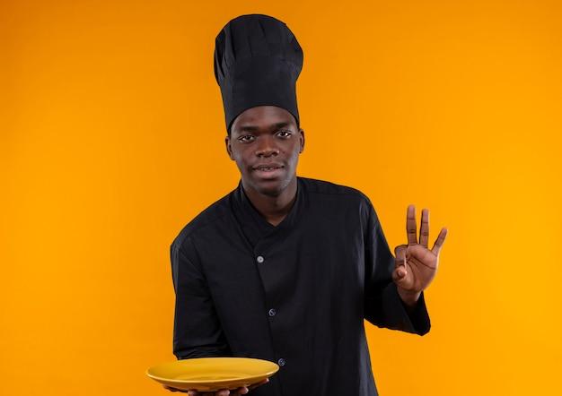 Jonge tevreden afro-amerikaanse kok in uniform chef houdt plaat en gebaren ok handteken op oranje met kopie ruimte