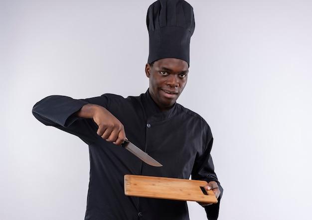 Jonge tevreden afro-amerikaanse kok in uniform chef houdt snijplank en punten met mes op wit met kopie ruimte