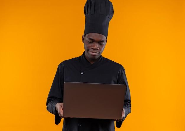 Jonge tevreden afro-amerikaanse kok in uniform chef-kok houdt en kijkt naar notitieblok op oranje met kopie ruimte
