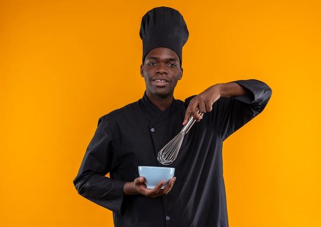 Jonge tevreden afro-amerikaanse kok in uniform chef-kok houdt klopper en kom camera kijken op oranje met kopie ruimte