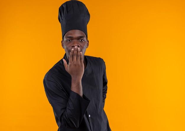 Jonge tevreden afro-amerikaanse kok in uniform chef legt hand op mond op oranje met kopie ruimte