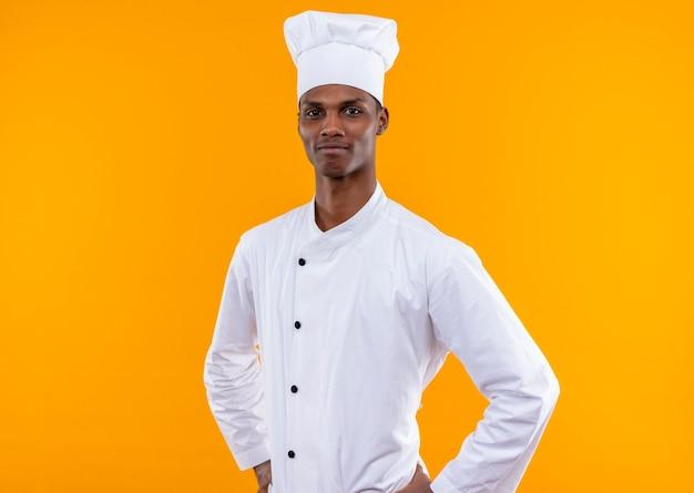 Jonge tevreden afro-amerikaanse kok in uniform chef legt handen op taille geïsoleerd op een oranje muur