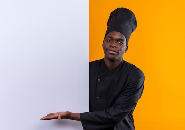 Jonge tevreden afro-amerikaanse kok in uniform chef staat achter en wijst naar witte muur op oranje met kopie ruimte