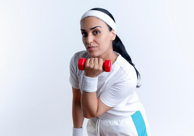Jonge tevreden blanke sportieve vrouw met hoofdband en polsbandjes houdt halter