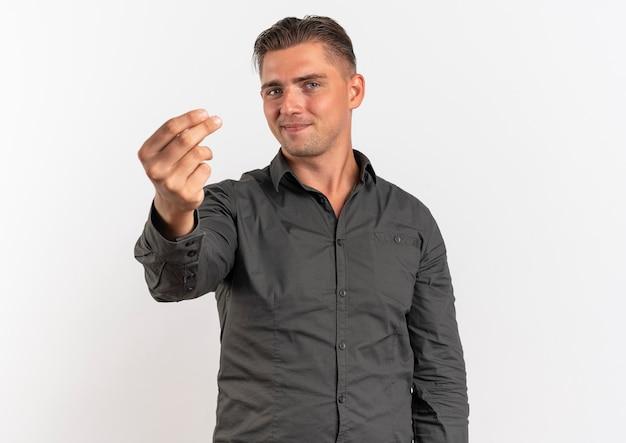Jonge tevreden blonde knappe man gebaren geld habd teken geïsoleerd op een witte achtergrond met kopie ruimte