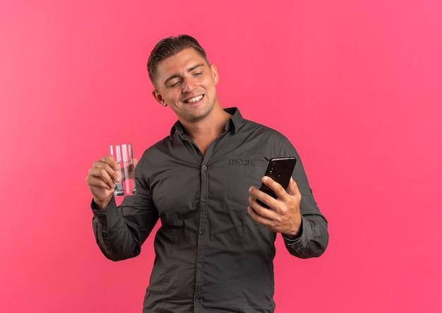 Jonge tevreden blonde knappe man houdt glas water en kijkt naar telefoon geïsoleerd op roze achtergrond met kopie ruimte