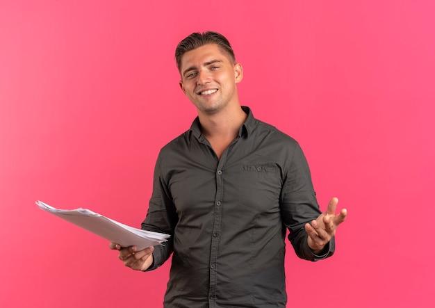 Jonge tevreden blonde knappe manholds vellen papier kijken camera geïsoleerd op roze achtergrond met kopie ruimte
