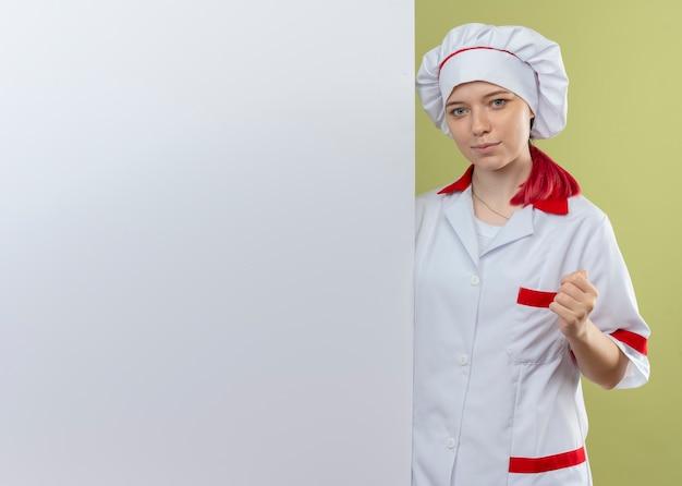 Jonge tevreden blonde vrouwelijke chef-kok in eenvormige chef-kok bevindt zich achter witte muur die op groene muur wordt geïsoleerd