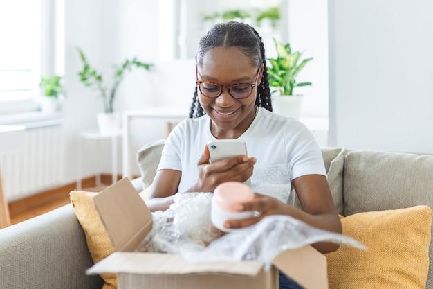 Jonge tevreden, gelukkig afrikaans meisje, vrouw, dame, shopaholic, klant, zitten, op, sofa, uitpakken, pakket, levering, box, online, shopping, verzending, concept. foto's van het product maken om op sociale media te plaatsen