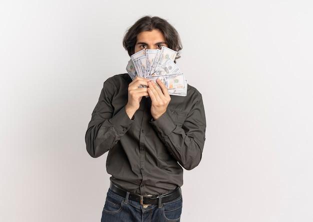 Jonge tevreden knappe blanke man houdt en kijkt door geld geïsoleerd op een witte achtergrond met kopie ruimte