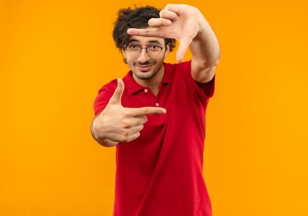 Jonge tevreden man in rood shirt met optische bril gebaren frame handteken geïsoleerd op oranje muur