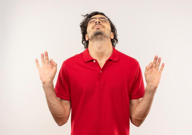 Jonge tevreden man in rood shirt met optische bril gebaren ok handteken en beweert te mediteren geïsoleerd op een witte muur