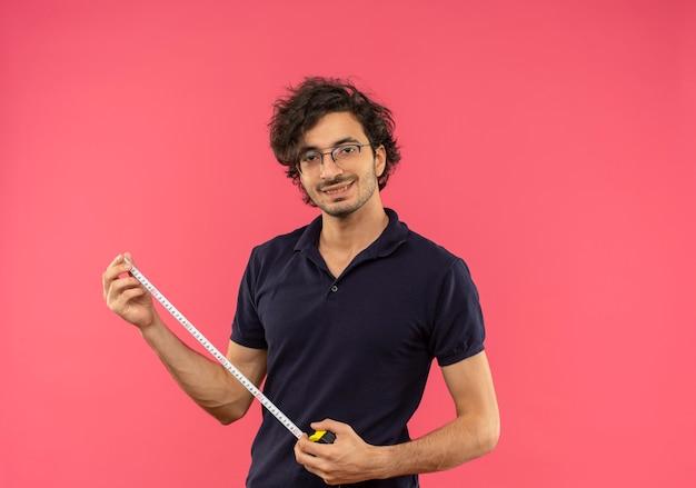 Jonge tevreden man in zwart shirt met optische bril houdt meetlint geïsoleerd op roze muur