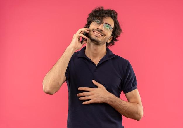 Jonge tevreden man in zwart shirt met optische bril praat over telefoon en legt hand op buik geïsoleerd op roze muur