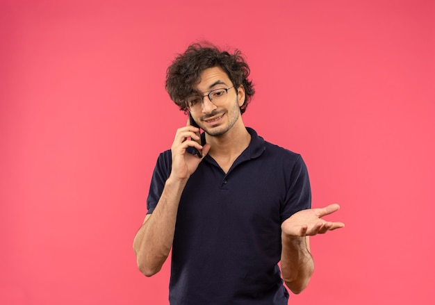 Jonge tevreden man in zwart shirt met optische bril praat over telefoon geïsoleerd op roze muur