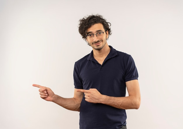 Jonge tevreden man in zwart shirt met optische bril wijst naar de zijkant en kijkt geïsoleerd op een witte muur