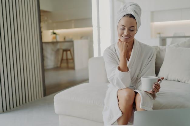 Jonge tevreden vrouw in badjas en haar gewikkeld in een handdoek kijkend naar laptopscherm en glimlachend zittend op de bank in de woonkamer, gelukkige vrouw ontspannen met een kopje thee na het douchen thuis