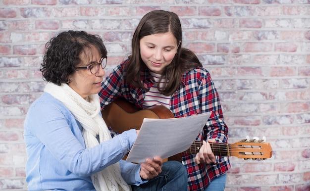 Jonge tiener die de gitaar met zijn leraar leert te spelen