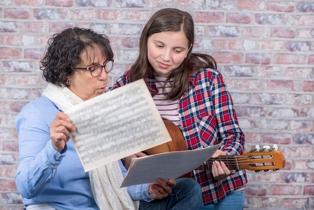 Jonge tiener die gitaar met zijn leraar leert te spelen