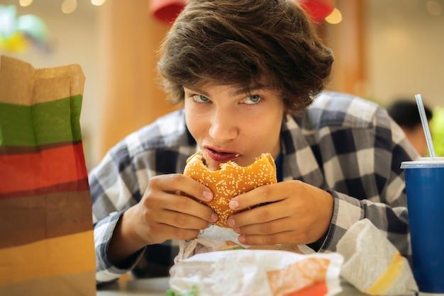 Jonge tiener die hamburger eet