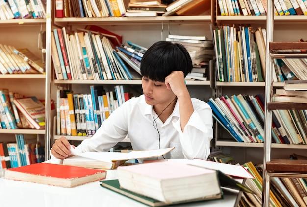 Jonge tiener die hoofdtelefoon op haar hoofd draagt, en gegevens van boek bij bibliotheek leest zoekt