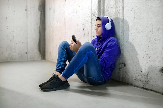 Jonge tiener die hoofdtelefoons draagt die op zijn mobiele telefoon babbelt aangezien hij op de concrete vloer in een metro zit