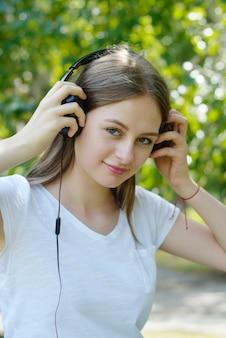 Jonge tiener het luisteren muziek met hoofdtelefoons en slimme telefoon in het park, de zomerportret.